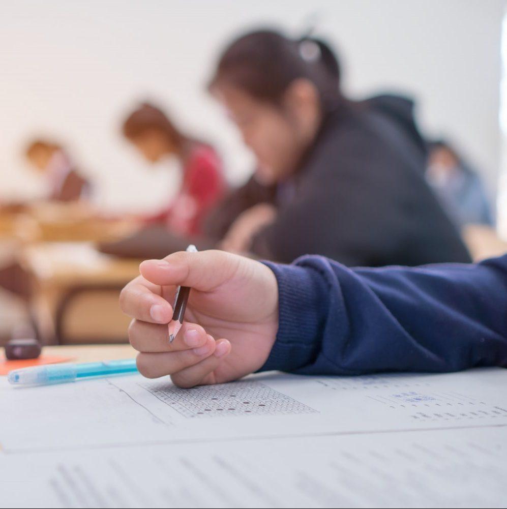 exams-test-student-high-school-university-student-holding-pencil-testing-exam-answer-sheet-min